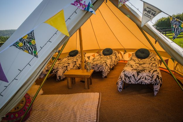 Interior shot of bell tent with cam beds, duvets and bunting