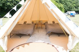 Wedding guest accommodation bell tent with double camp beds and bunting