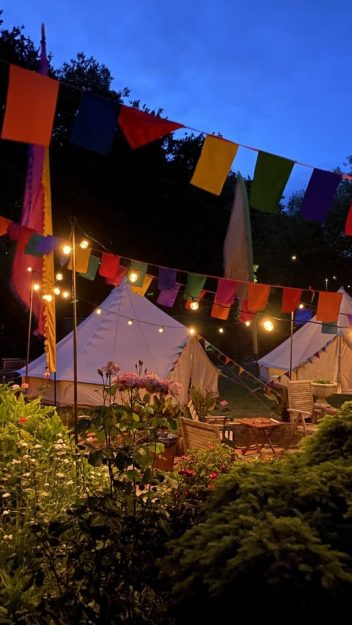 Garden glamping in Hampshire, outside photo of bell tent, festoons and flags