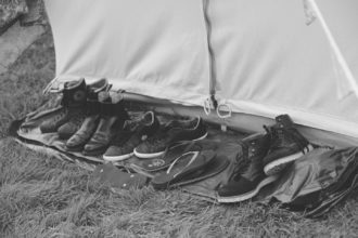 Collection of shoes outside a wedding guest bell tent