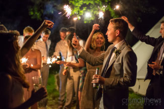 Real wedding: Wedding guests enjoying sparklers amongst the bell tent gleaming village