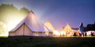 Real ending: 7m bell tent lit up at night for a festival tipi wedding