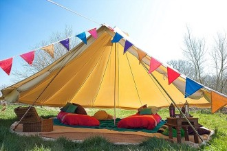 5m bell tent with the sides rolled up and dressed in Moroccan colourful style