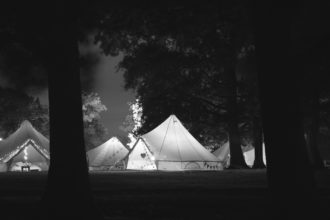 Bell tents viewed at night with the tents lit up