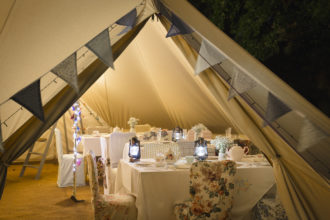 Bell tent set up with tables and chairs for a vintage tea party