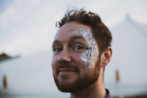 Wedding Glamping in Hampshire. Man with festival face paint.