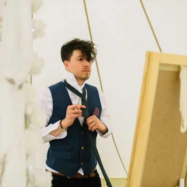 Groom dressing in wedding bell tent