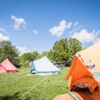 Outside shot fo coloured bell tents at Hen camp