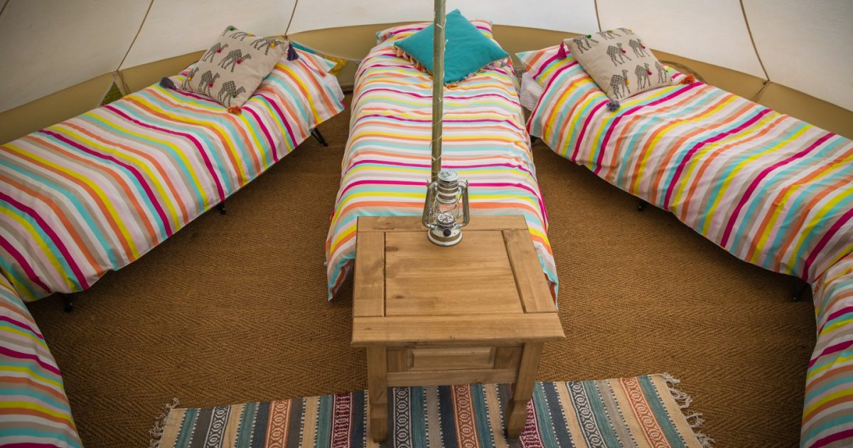 Interior shot fo hen camp sleeping tent with striped bedding