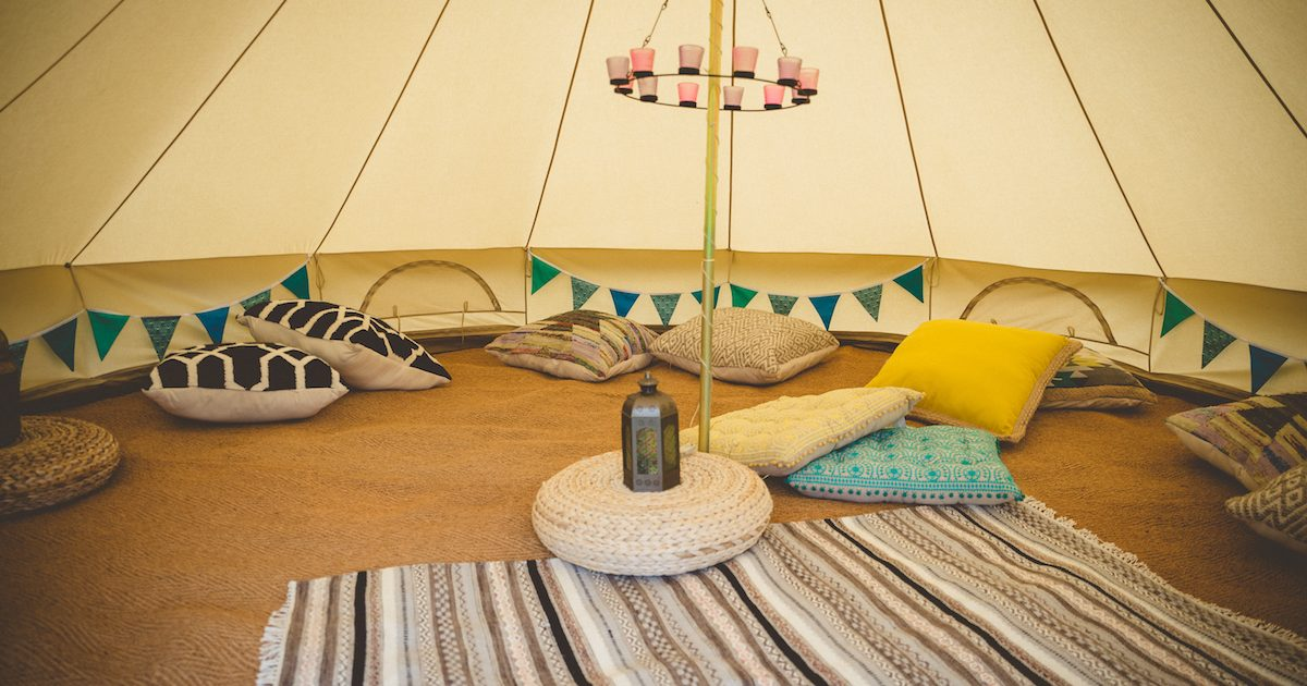 5m chill out bell tent with cushions, rugs and tea-light chandelier. Bell tents for chill out time in West Sussex.