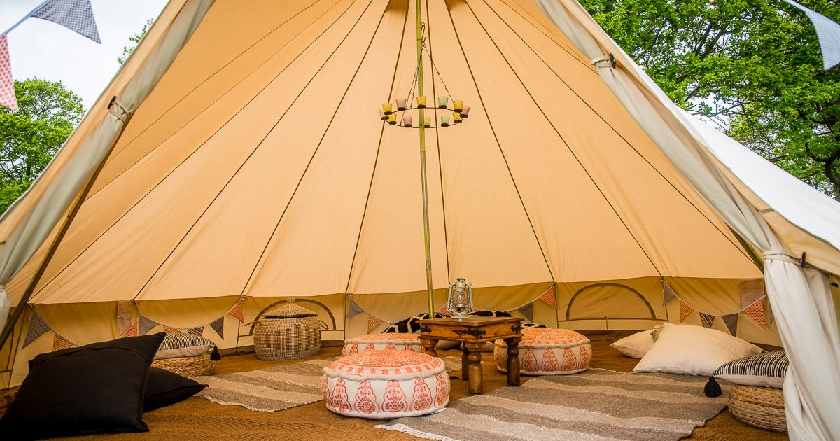 7m chill out bell tent with tea-light chandelier and floor cushions. Chill out bell tent hire West Sussex.