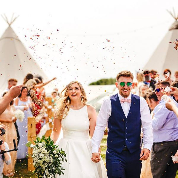 Abi and Greg walking through confetti. Outdoor wedding inspiration. Bell tent hire West Sussex
