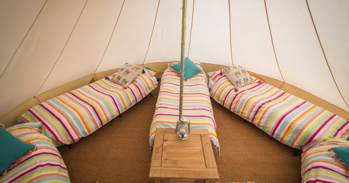 Camp beds and colourful duvets in one of our hen party accommodation bell tents at hen camp in Dorset