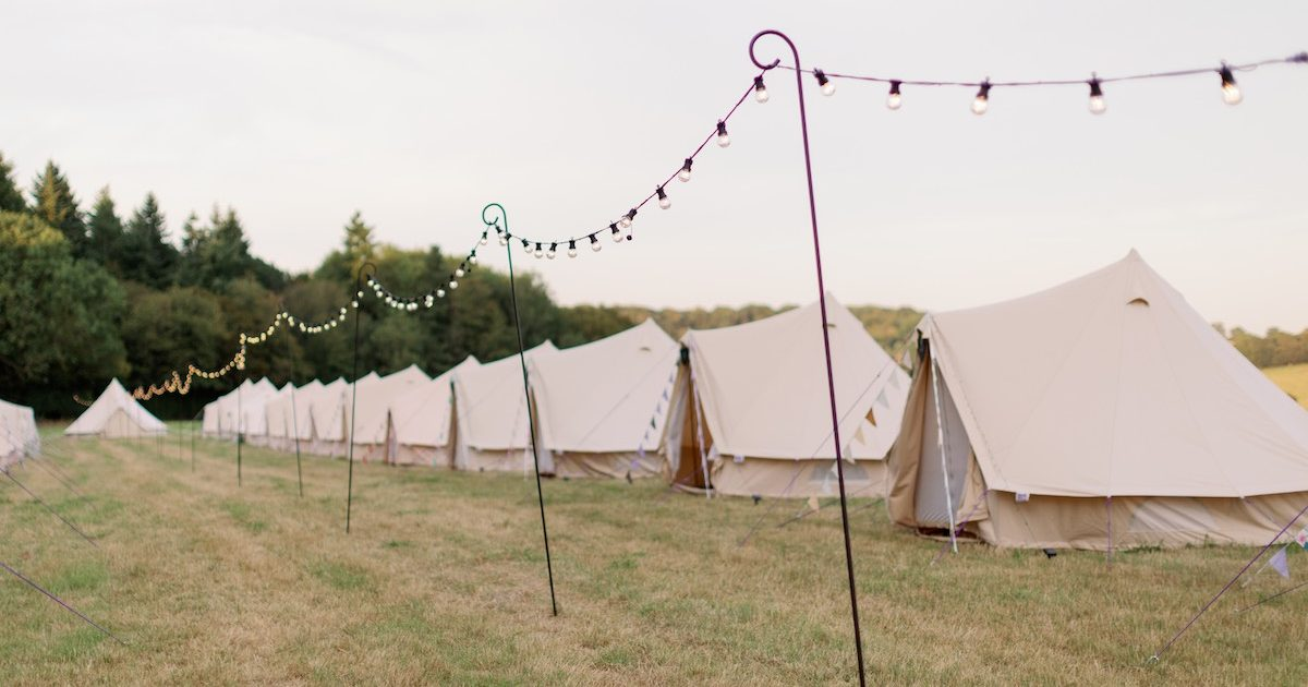 Row of bell tent with festoon lights running through the middle. Bell tent hire for weddings in Surrey.