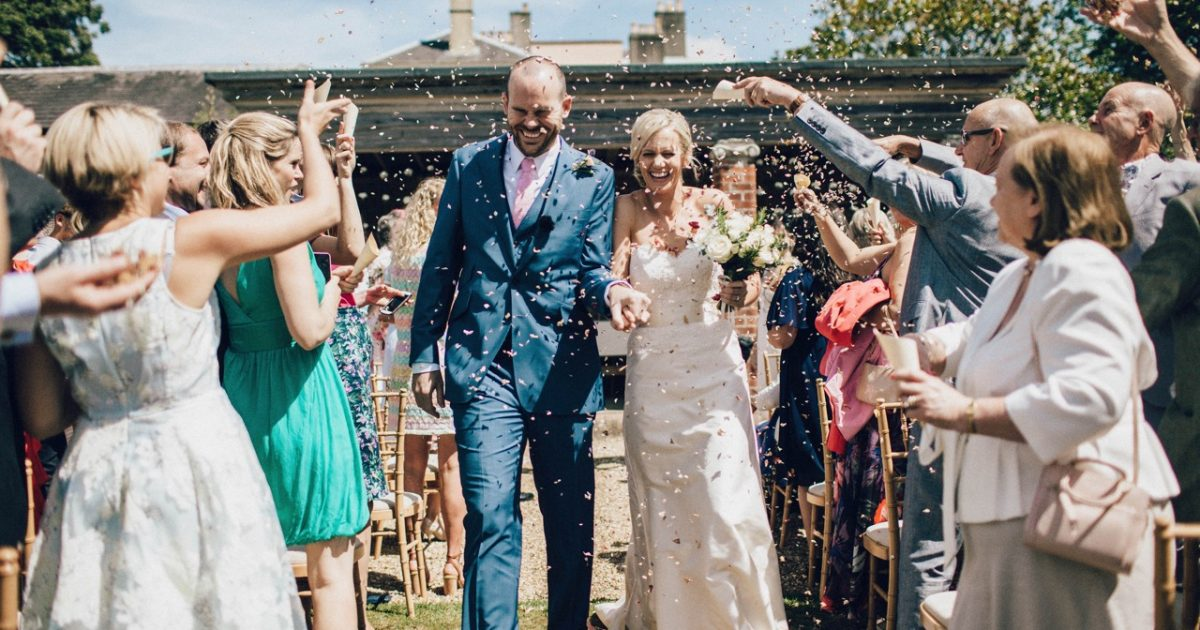 Couple just married with confetti being thrown at Bignor Park
