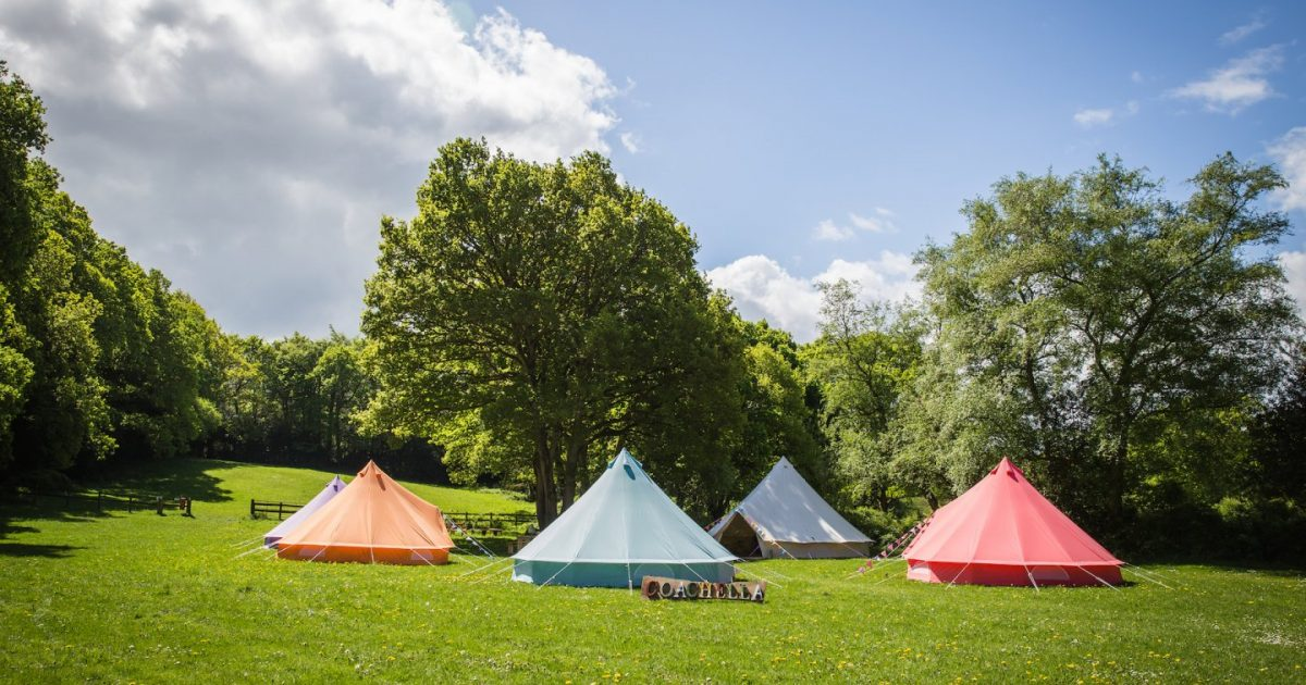 Exterior picture showing coloured bell tents for Coachella (now Tropic) hen camp area. Luxury glamping for hen parties. See more in our hen camp gallery