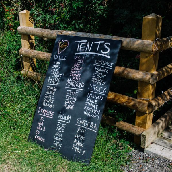 Black board with tent names written on for guests. Bell tent hire, The Secret Barn, West Sussex. Outdoor wedding inspiration.