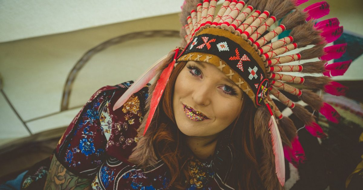 Hen in feathered headdress. Tips for planning a glamping hen party