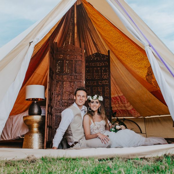 Bride and groom sat in doorway of Boho wedding tent. Glamping wedding bell tent hire in Surrey. Green Union sustainable wedding blog.