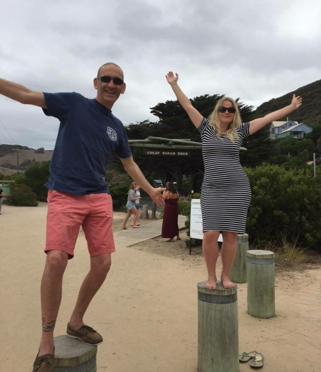About us: Picture of Katrina and Steve from Beautiful Bells stood on posts as they went camping on the Great Ocean Road, Australia.