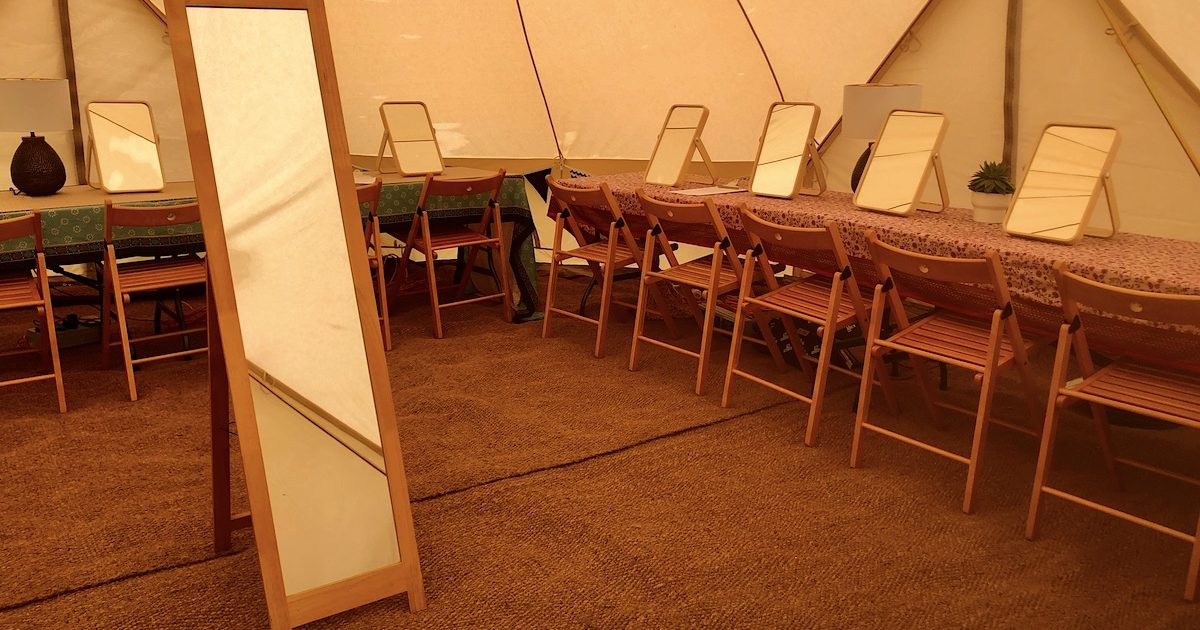 Interior of 7m pamper bell tent with full length mirror and trestle tables. Pamper tent hire for weddings and events.