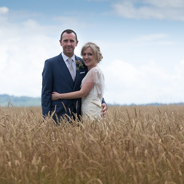 Paula and Jon stood in corn field. Bell tent hire, Surrey