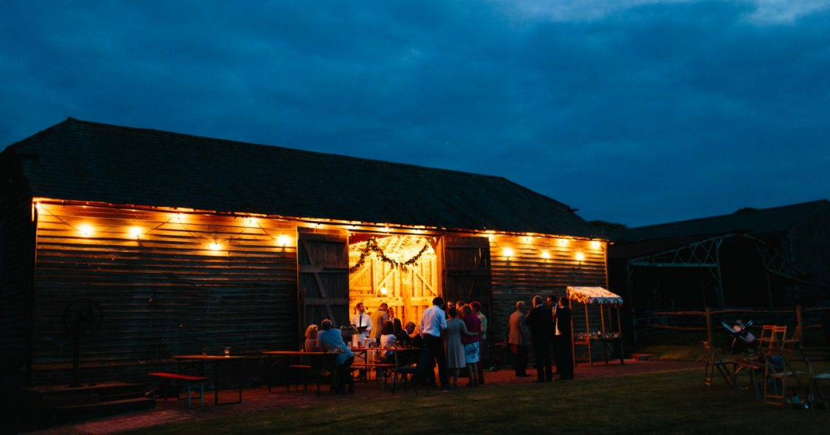 Night shot of the Secret Barn lit up with festoon lights