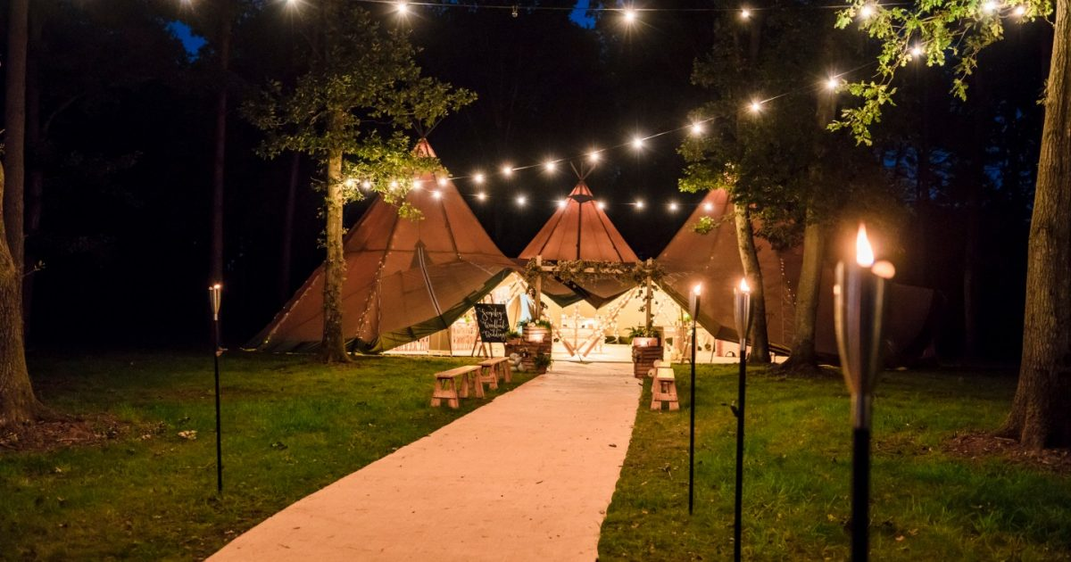 Tipis at night, lit up with festoons, at Somerley Woodland weddings
