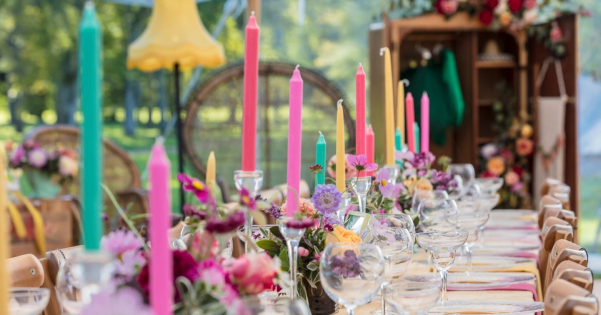 Inside of marque with bright coloured candles and flowers