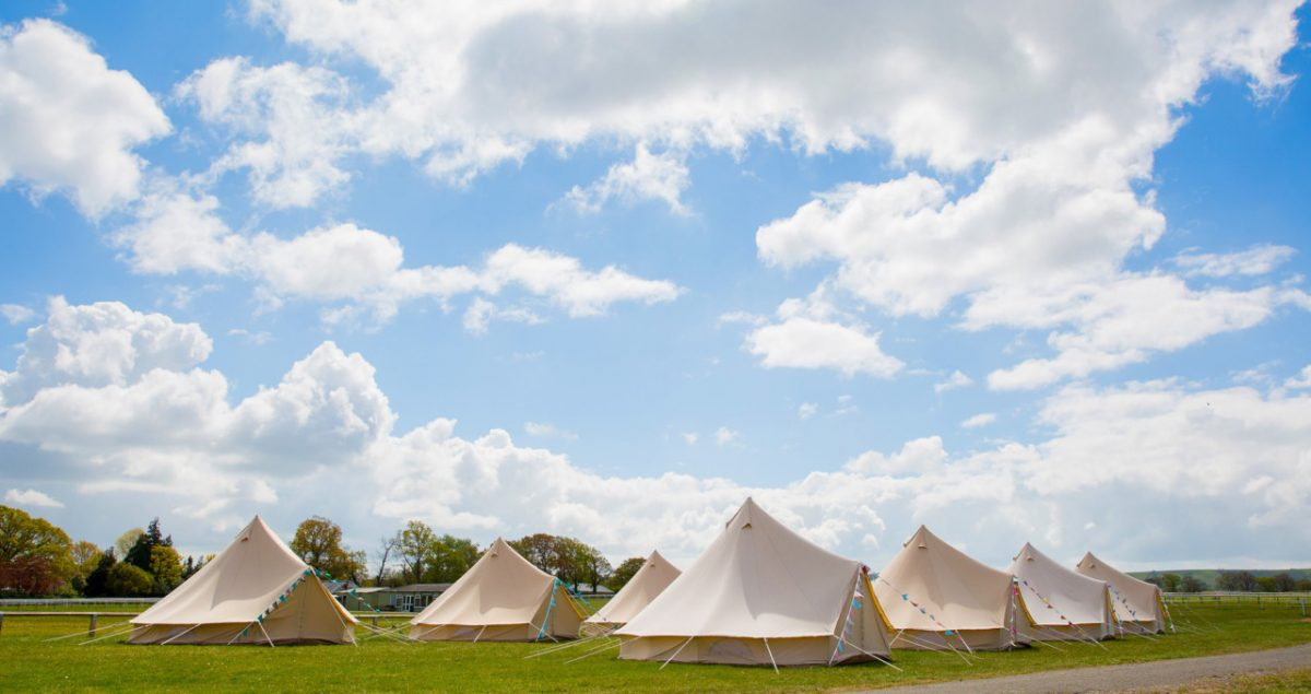 Bell tent village on the racecourse with blue skies at Plumpton Racecourse