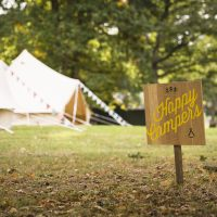 Outside shot of bell tents set up for corporate booking with 'happy camping' sign