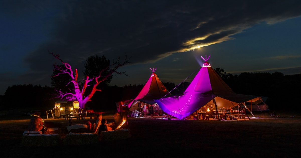 Kata tipis at night, lit up in purples at Fiesta Fields