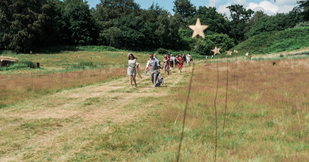 Guests walking through field with star lined path towards outdoor wedding reception to bell tents