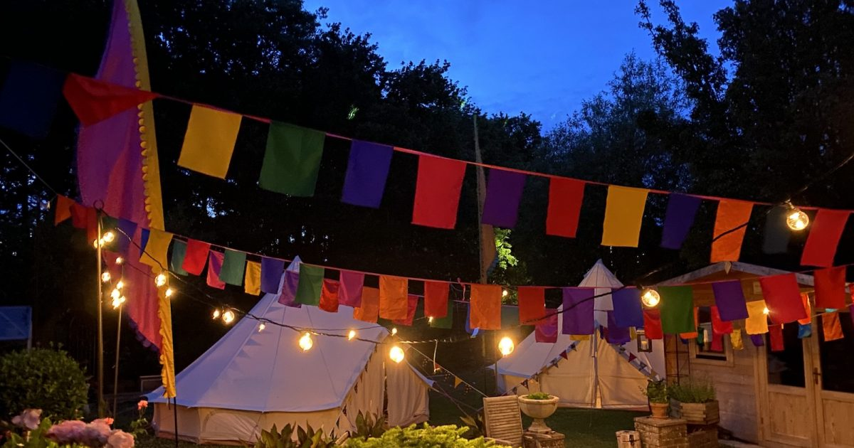 Garden glamping wiht festoons and bell tents and bunting. In Hampshire West Sussex and Surrey.