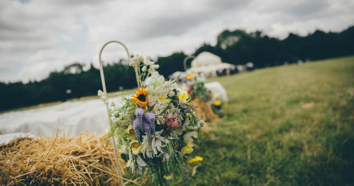 Outdoor shot of hay bales with flowers ready for an outside wedding reception.Bell tent hire at Fiesta Fields