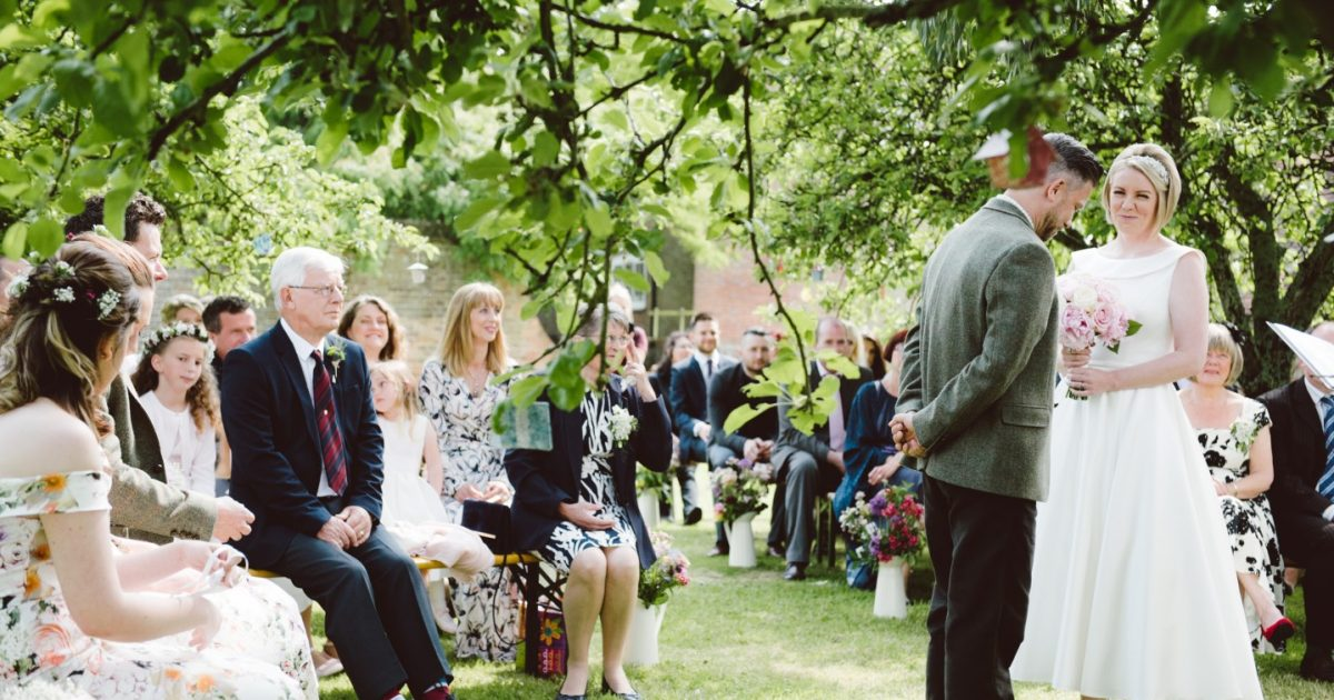 Couple getting married in the orchard at The Secret Barn with guess watching