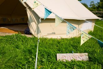 Bell tent village, 4m bell tent with bright bunting and wooden signage