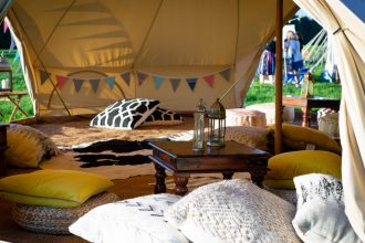 Our 4 door 7m chill out bell tent with lots of floor cushions and wooden tables