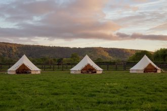3 cream bell tents set up for glamping holidays